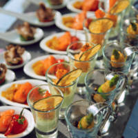 Spoons and glasses with seafood snacks on banquet table